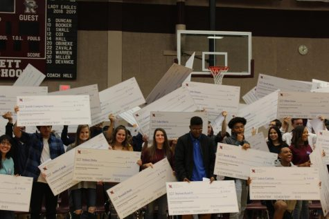 NMSI students receive check for passing their AP test in English, math, or science during a pep rally that celebrates their academic success.